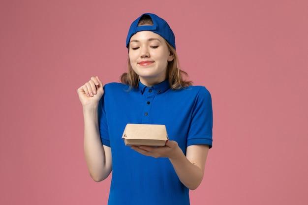 淡いピンクの壁に小さな配達食品パッケージを保持している青い制服と岬の正面図の女性の宅配便、配達制服労働者サービスの従業員