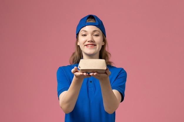 淡いピンクの壁に小さな配達食品パッケージを保持している青い制服と岬の正面図女性宅配便、配達作業制服サービス従業員
