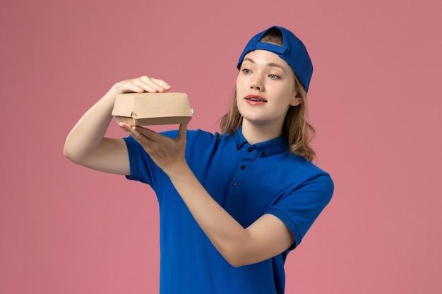 淡いピンクの壁に小さな配達食品パッケージを保持している青い制服と岬の正面図女性宅配便、仕事配達制服サービス従業員