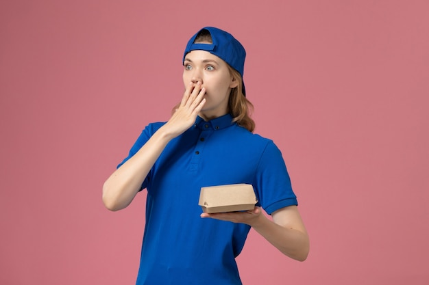 ピンクの背景に小さな配達食品パッケージを保持している青い制服と岬の正面図女性宅配便配達制服サービス会社の労働者の女の子の仕事