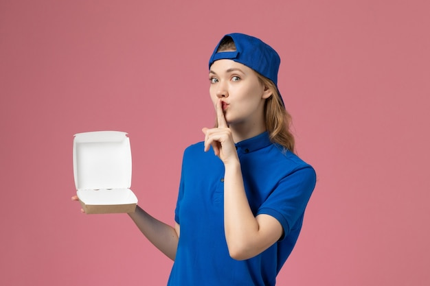 青いユニフォームとピンクの背景に小さな配達食品パッケージを保持している岬の正面図の女性の宅配便配達制服サービスの仕事の従業員