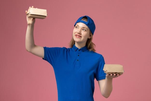 Вид спереди курьер-женщина в синей форме и накидке с маленькими пакетами с доставкой на розовой стене, служба доставки, рабочая форма, сервисная компания