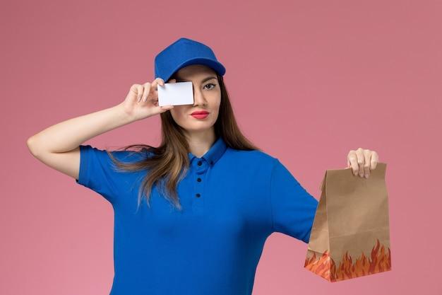 Женщина-курьер в синей форме и плаще, держащая белую карточку и бумажный пакет с едой на розовой стене, вид спереди