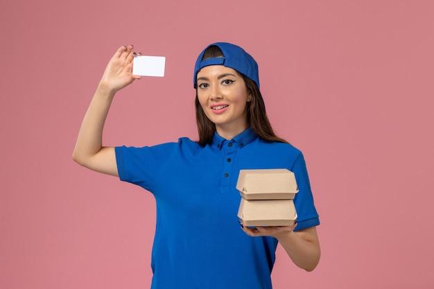 青い制服の岬の保持カードと淡いピンクの壁に小さな配達パッケージの正面図の女性の宅配便、サービス従業員の配達
