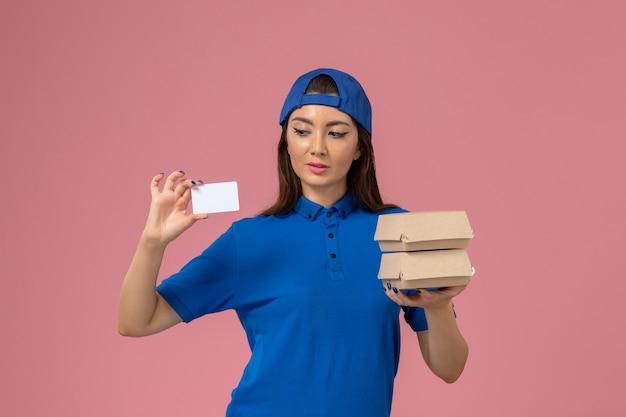 青い制服の岬の保持カードと淡いピンクの壁に小さな配達パッケージの正面図の女性の宅配便、サービスジョブ従業員の配達
