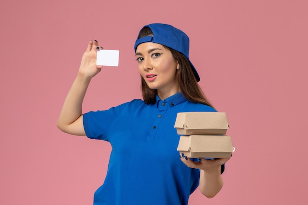 青い制服のケープホールディングカードと淡いピンクの壁に小さな配達パッケージの正面図の女性の宅配便、サービスワーカーの従業員の配達