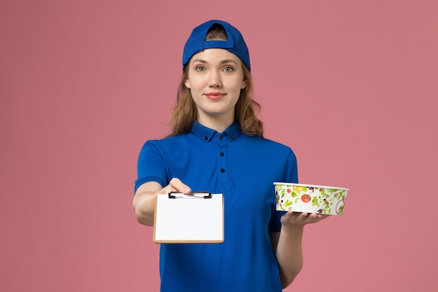 淡いピンクの壁に配達ボウルとメモ帳を保持している青い制服ケープの正面図女性宅配便、ジョブサービス配達従業員