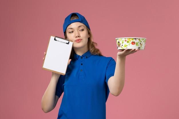 淡いピンクの壁に配達ボウルとメモ帳を保持している青い制服ケープの正面図女性宅配便、サービス配達従業員の仕事