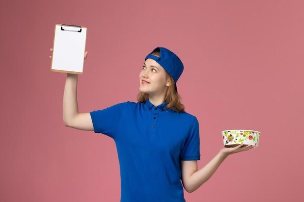 淡いピンクの壁に配達ボウルとメモ帳を保持している青い制服ケープの正面図女性宅配便、サービス配達従業員労働者