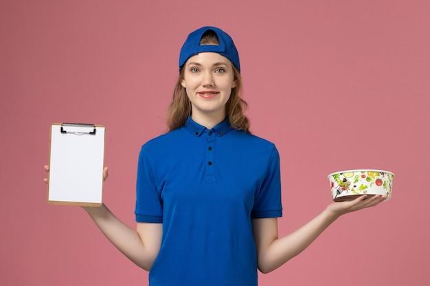 淡いピンクの壁に配達ボウルとメモ帳を保持している青い制服ケープの正面図女性宅配便、サービス配達従業員