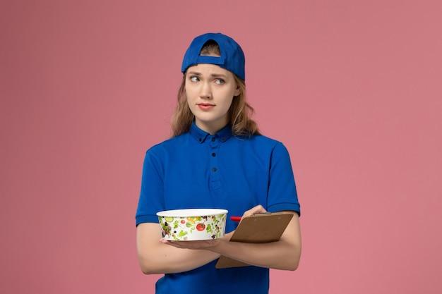 淡いピンクの壁に配達ボウルとメモ帳を保持している青い制服ケープの正面図女性宅配便、サービス配達仕事の従業員