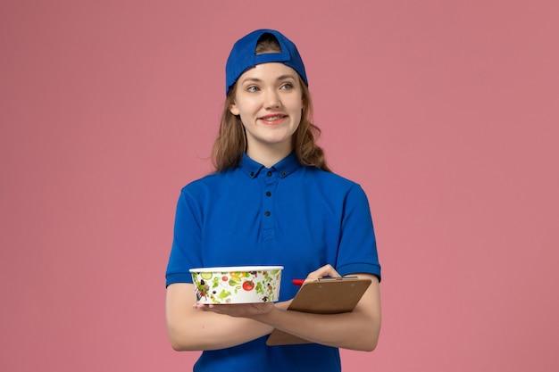 淡いピンクの壁に配達ボウルとメモ帳を保持している青い制服ケープの正面図女性宅配便、サービス作業配達従業員