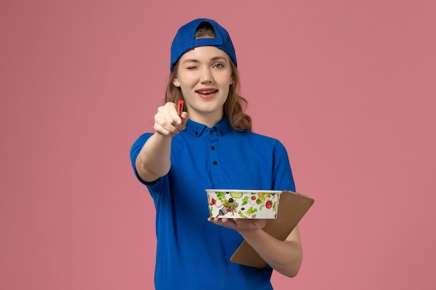 淡いピンクの壁に配達ボウルとメモ帳のペンを保持している青い制服ケープの正面図女性宅配便、サービス配達作業員