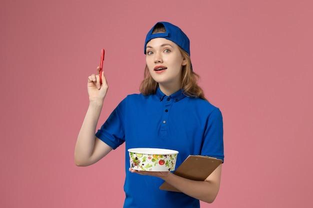 淡いピンクの壁に配達ボウルとメモ帳のペンを保持している青い制服ケープの正面図女性宅配便、サービス配達労働者の従業員
