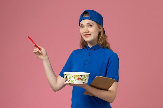 淡いピンクの壁に配達ボウルとメモ帳のペンを保持している青い制服ケープの正面図女性宅配便、作業サービス配達従業員