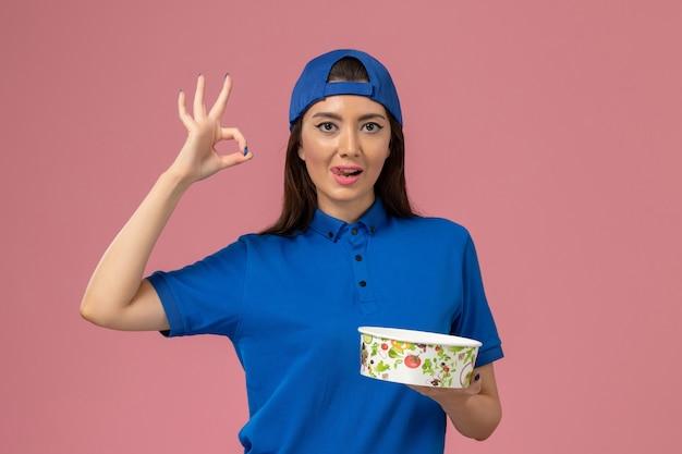 淡いピンクの壁に配達ボウルを保持している青い制服ケープの正面図女性宅配便、作業サービス従業員の配達