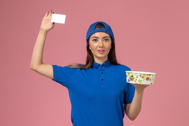 淡いピンクの壁にカード付きの配達ボウルを保持している青い制服ケープの正面図女性宅配便、ジョブサービス従業員の配達