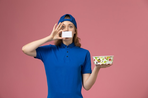 淡いピンクの壁にカードと配達ボウルを保持している青い制服ケープの正面図女性宅配便、サービス配達従業員の仕事