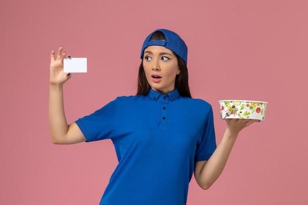 淡いピンクの壁にカードと配達ボウルを保持している青い制服ケープの正面図女性宅配便、サービス従業員の配達作業の仕事