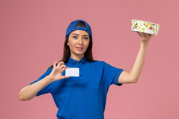 淡いピンクの壁にカード付きの配達ボウルを保持している青い制服ケープの正面図女性宅配便、サービス従業員の配達作業