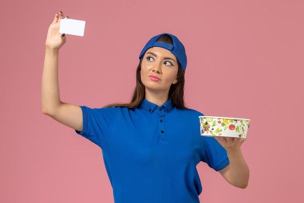 淡いピンクの壁にカードと配達ボウルを保持している青い制服の岬の正面図の女性の宅配便、サービス従業員の配達員