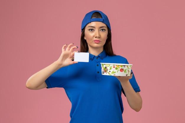 淡いピンクの壁にカードと配達ボウルを保持している青い制服ケープの正面図女性宅配便、サービス従業員の配達