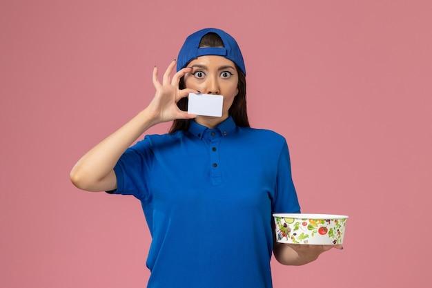淡いピンクの壁にカードと配達ボウルを保持している青い制服ケープの正面図女性宅配便、サービス従業員の仕事の配達