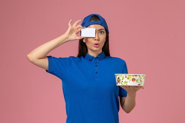 淡いピンクの壁にカードと配達ボウルを保持している青い制服ケープの正面図の女性の宅配便、サービス作業の仕事の従業員の配達