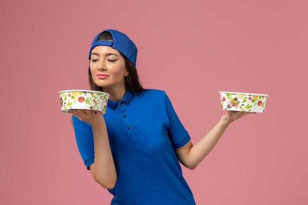 淡いピンクの壁に臭いがする配達ボウルを保持している青い制服ケープの正面図女性宅配便、サービス従業員の配達