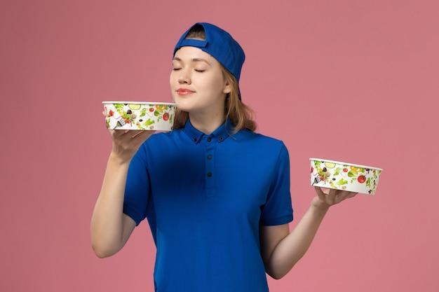 ピンクの壁に臭いがする配達ボウルを保持している青い制服ケープの正面図女性宅配便、サービス配達従業員