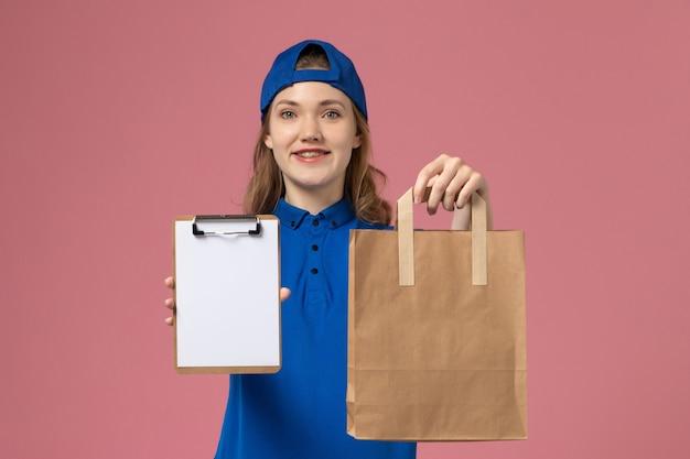 Женщина-курьер в синей форме, держащая посылку с доставкой и блокнот на розовой стене, вид спереди, служба доставки сотрудников