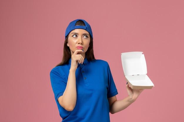 ピンクの壁に空の小さな配達パッケージを保持している青い制服ケープの正面図女性宅配便、従業員サービス会社の配達