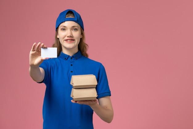 ピンクの背景のサービス配達従業員の仕事に小さな配達食品パッケージとカードを保持している青い制服ケープの正面図女性宅配便