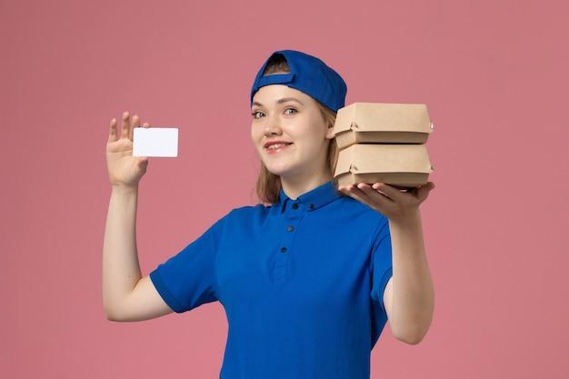 ピンクの背景のサービス配達従業員労働者に小さな配達食品パッケージとカードを保持している青い制服ケープの正面図女性宅配便