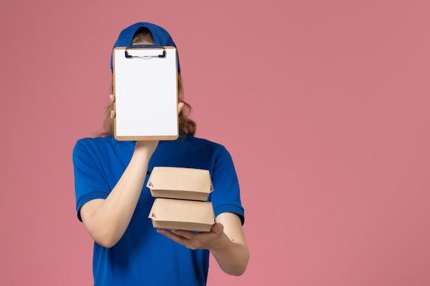 淡いピンクの背景の配達サービスの従業員に小さな配達食品パッケージとメモ帳を保持している青い制服の岬の正面図の女性の宅配便