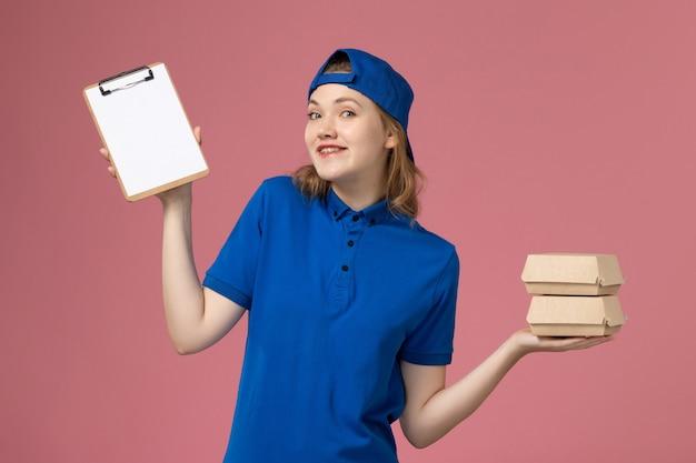 Вид спереди женщина-курьер в синей форменной накидке с маленькими пакетами с доставкой еды и блокнотом на розовом фоне работа сотрудника службы доставки