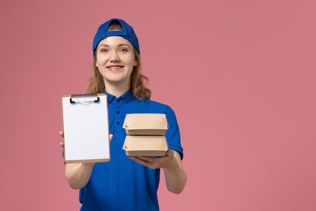 Женщина-курьер в синей форме, держащая маленькие пакеты с едой и блокнотом на розовом фоне, сотрудник службы доставки