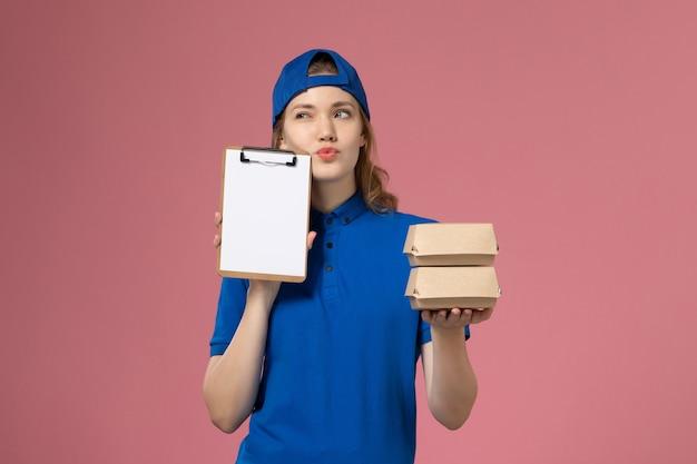 Женщина-курьер в синей форме, держащая маленькие пакеты с доставкой еды и блокнот, думает о сотруднике службы доставки на розовом фоне
