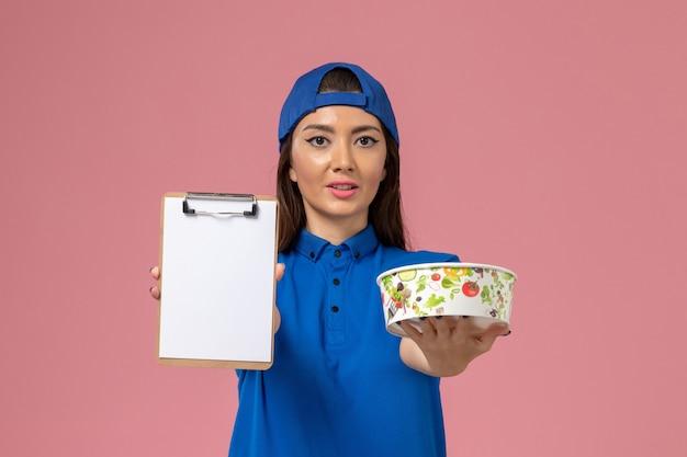 밝은 분홍색 벽, 소녀 서비스 직원 배달에 배달 그릇 메모장을 들고 파란색 유니폼 케이프에서 전면보기 여성 택배
