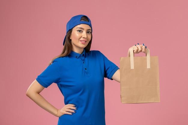 Женщина-курьер в синей форменной накидке, держащая пакет для доставки бумаги на светло-розовой стене, вид спереди, сотрудник службы доставки
