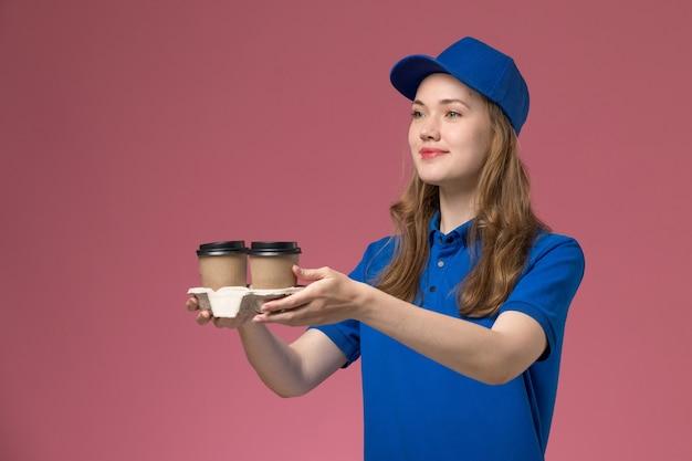 Вид спереди женщина-курьер в синей форме, доставляющая коричневые кофейные чашки на розовом фоне, сервисная форма, доставляющая работу компании