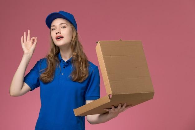 Вид спереди женщина-курьер в синей униформе держит пустую коробку для доставки еды на розовом столе.