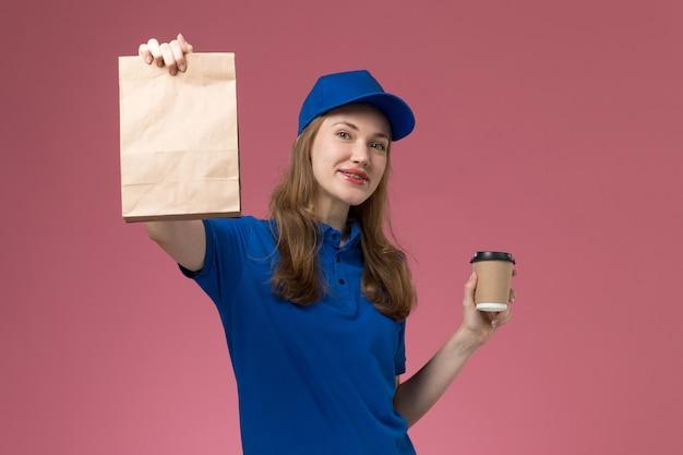 淡いピンクのデスクサービスの仕事の制服の配達会社に食品パッケージと茶色のコーヒーカップを保持している青い制服の正面図の女性の宅配便