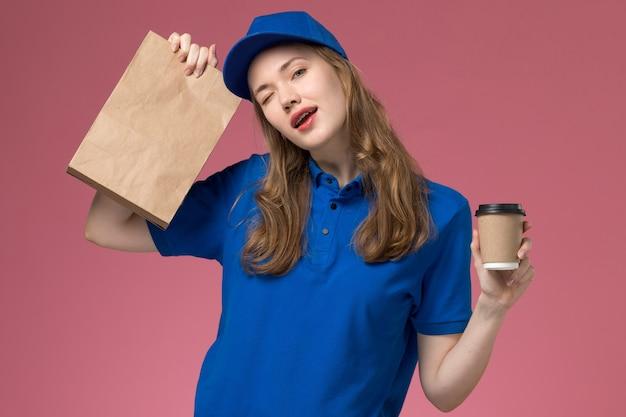 Вид спереди курьер-женщина в синей форме, держащая коричневую кофейную чашку с пакетом продуктов на розовом столе, служба доставки униформы