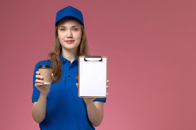 淡いピンクのフロアサービスの仕事の制服の配達会社にメモ帳付きの茶色のコーヒーカップを保持している青い制服の正面図の女性の宅配便