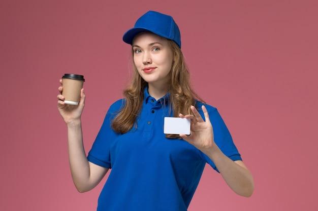 Вид спереди женщина-курьер в синей форме, держащая коричневую кофейную чашку с белой карточкой на светло-розовом столе, сервисная рабочая форма, доставка компании