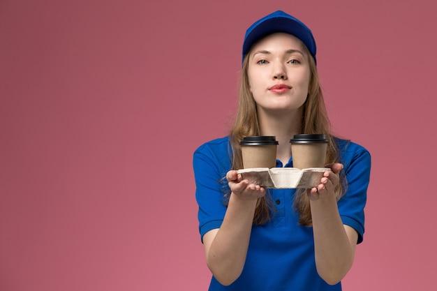 Вид спереди женщина-курьер в синей форме держит коричневые кофейные чашки, доставляя их на розовом фоне, сервисная форма, доставляющая работу компании