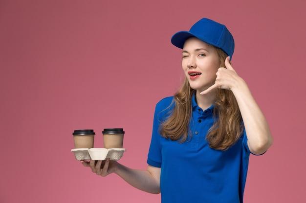 茶色のコーヒーカップを保持している青い制服を着た正面図の女性の宅配便は、会社の仕事を提供するピンクのデスクサービスの制服でshowign電話ジェスチャーをウィンクします