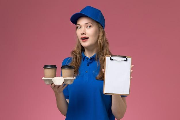Вид спереди женщина-курьер в синей униформе с коричневыми кофейными чашками и блокнотом на розовом столе.