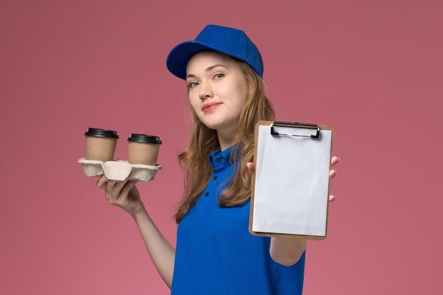 Вид спереди женщина-курьер в синей униформе с коричневыми кофейными чашками и блокнотом с улыбкой на розовом столе.